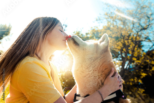 Young woman kissing her dog in the park at sunset - Love between people and dogs  - fototapety na wymiar
