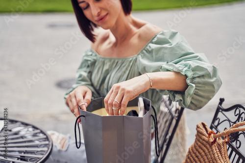 Obraz Girl opening paper bag in restaurant - fototapety do salonu