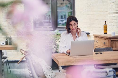 Obraz Pritty business woman working on laptop in restaurant - fototapety do salonu