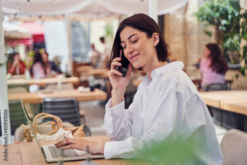 Obraz Pritty business woman talking on phone and drinking cocktail - fototapety do salonu