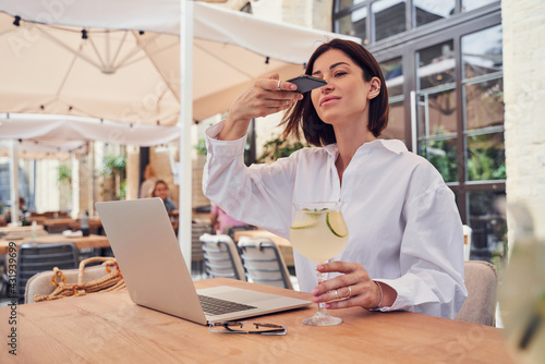 Obraz Girl taking photo of laptop with by phone in restaurant - fototapety do salonu