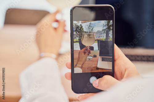 Obraz Close up shot of girl taking photo of laptop with by phone in restaurant - fototapety do salonu