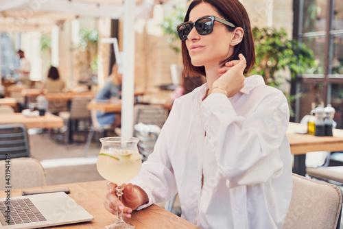 Obraz POrtrait of business woman in glasses drinking cocktail - fototapety do salonu