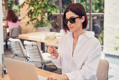 Obraz Pritty business woman in glasses drinking cocktail - fototapety do salonu