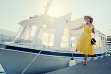 Travel By Greece. Pretty Young Traveling Woman In Ellow Dress Boarding On Ferry Boat Taxi, Poros Island.