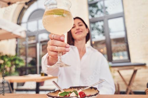 Obraz Attractive girl drinking aperol in restaurant cocktail - fototapety do salonu