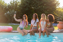Cheerful Female Friends Taking Selfie Through Mobile Phone While Sitting At Swimming Pool During Sunny Day