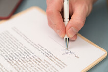 Close-up Of Businessman Giving Signature On Contract Paper At Home