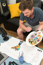 Artist Painting Doodle On T-shirt While Live Streaming At Home