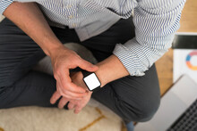 Businessman Using Smart Watch While Sitting At Home