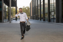 Smiling Businessman With Briefcase Talking On Mobile Phone While Walking On Footpath