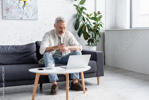 Obraz bearded man pointing at laptop while sitting on couch near cup of coffee and smartphone with blank screen on coffee table. - fototapety do salonu