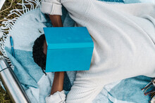Young Man Taking Nap While Covering His Face With A Book