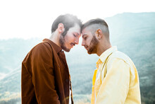 Gay Couple With Eyes Closed Standing Face To Face Against Sky