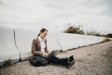 Female Entrepreneur Working On Laptop While Sitting By Crash Barrier At Roadside