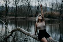 Blond Woman Sitting On Fallen Tree Against Lake