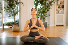 Slim Woman Meditating With Clasped Hands At Home