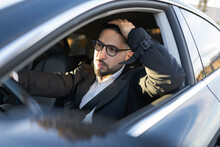 Male Entrepreneur With Hand In Hair Looking Away While Driving Car