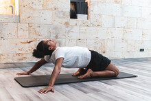 Male Hipster Stretching On Mat While Exercising At Yoga Studio