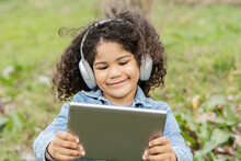 Boy Using Digital Tablet While Listening Music In Nature