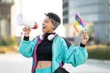 Female LGBTQIA Protestor Holding Rainbow Flag While Announcing Through Megaphone