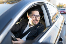 Smiling Businessman Looking Away While Driving Car