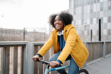 Smiling Woman Cycling On Footpath