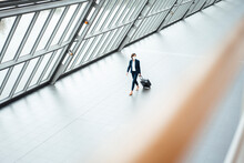 Businesswoman With Suit Case Walking In Corridor During COVID-19