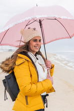 Portrait Of Young Woman Standing At Beach With Umbrella In Hands