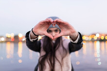 Teenage Girl Doing Heart With Her Hands During Sunset