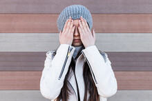 Teenage Girl Covering Her Face With Hands While Standing Against Wall