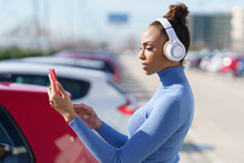 Young Woman Wearing Headphones Using Mobile Phone While Standing At Parking Lot