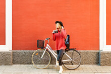 Young Woman Wearing Hat Holding Vintage Camera While Standing With Bicycle Against Red Wall
