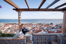 Traveling By Portugal. Young Traveling Woman Enjoying Old Town Lisbon View, Red Tiled Roofs, Ancient Architecture And River.