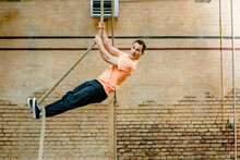 Male Man Hanging On Rope By Brick Wall At Gym