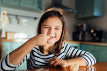 Smiling Girl Eating Tangerine While Sitting At Dining Table In Kitchen