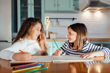 Smiling Girls Looking At Each Other While Coloring With Colored Pencil On Paper While Sitting At Dining Table In Kitchen