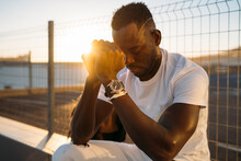 Worried African Man Sitting Against Fence During Sunset