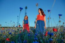 Beautiful Women Standing In Poppy Field Against Clear Blue Sky