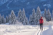 Female Explorer With Ski Pole Skiing Over Snow Mountain During Winter
