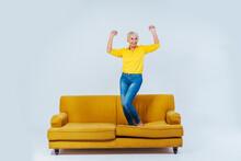 Cheerful Senior Woman Dancing On Sofa While Listening Music Through Wireless Headphones Against White Background
