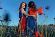 Woman With Arm Around Waist Of Female Friend Standing In Poppy Field