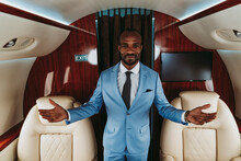 Smiling Male Entrepreneur Gesturing While Standing Amidst Seats In Private Jet