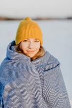 Portrait Of Beautiful Teenage Girl Wearing Knit Hat Warming Herself Up With Wool Blanket