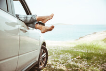 Woman Legs Stick Out From Car Window Sea Beach On Background