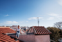 Traveling By Portugal. Young Traveling Woman Enjoying Old Town Lisbon View On Red Tiled Roof.