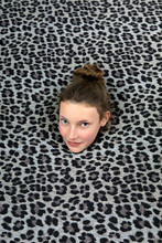 Studio Shot Of Head Of Teenage Girl Sticking Out Of Leopard Print
