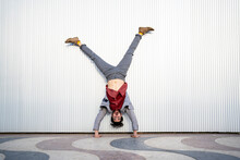 Businessman Doing Handstand On Footpath In Front Of Wall
