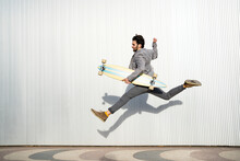 Graceful Man Jumping High With Longboard On Footpath By Wall