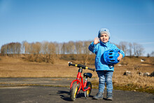 Cute Boy With Cycling Helmet Waving Hand While Standing By Balance Bike On Road